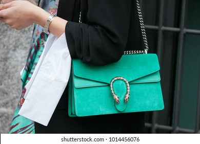 MILAN - JANUARY 15: Woman with turquoise blue Gucci bag and scarf before Giorgio Armani fashion show, Milan Fashion Week street style on January 15, 2018 in Milan.