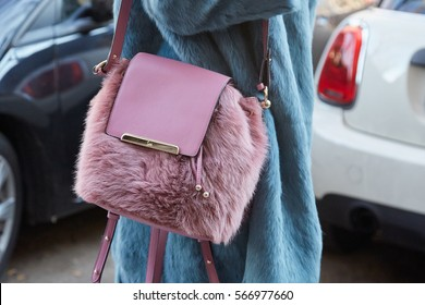 MILAN - JANUARY 16: Woman with pink fur Louboutin bag and blue fur coat before Cedric Charlier fashion show, Milan Fashion Week street style on January 16, 2017 in Milan.