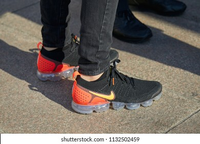 MILAN - JUNE 15: Man with black and orange Nike sneakers before Alberta Ferretti fashion show, Milan Fashion Week street style on June 15, 2018 in Milan.