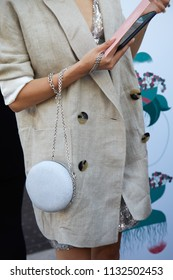 MILAN - JUNE 15: Woman with beige jacket and glitter round bag with silver chain before Alberta Ferretti fashion show, Milan Fashion Week street style on June 15, 2018 in Milan.