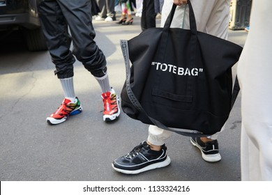 MILAN - JUNE 16: Man with black Off White tote bag and man with red shoes before Marni fashion show, Milan Fashion Week street style on June 16, 2018 in Milan.