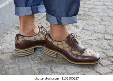 MILAN - JUNE 16: Man with brown leather Gucci shoes and blue jeans before Marni fashion show, Milan Fashion Week street style on June 16, 2018 in Milan.