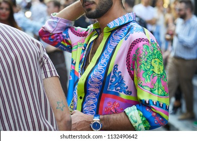 MILAN - JUNE 16: Man with colorful Versace shirt with green Medusa head before Versace fashion show, Milan Fashion Week street style on June 16, 2018 in Milan.