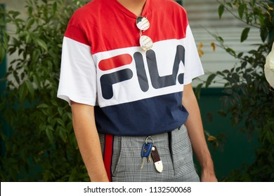 MILAN - JUNE 16: Man with Fila shirt in red, white and blue colors before Marni fashion show, Milan Fashion Week street style on June 16, 2018 in Milan.