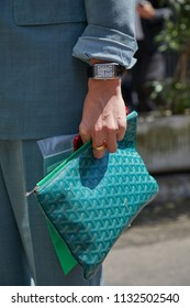 MILAN - JUNE 16: Man with green Goyard bag Jaeger Le coultre Reverso watch before Marni fashion show, Milan Fashion Week street style on June 16, 2018 in Milan.