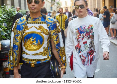 MILAN - JUNE 16: Men with Versace shirt and jacket with golden decorations and man with purple braids before Versace fashion show, Milan Fashion Week street style on June 16, 2018 in Milan.