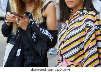 MILAN - JUNE 16: Woman with black Versace jacket and woman with striped dress in yellow, pink and white before Marni fashion show, Milan Fashion Week street style on June 16, 2018 in Milan.