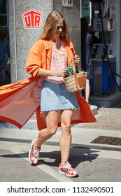 MILAN - JUNE 16: Woman with orange trench coat and Loewe wicker bag before Marni fashion show, Milan Fashion Week street style on June 16, 2018 in Milan.