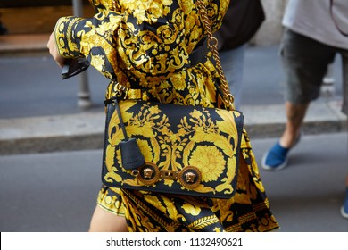 MILAN - JUNE 16: Woman with Versace dress and bag with golden floral decoration on black before Versace fashion show, Milan Fashion Week street style on June 16, 2018 in Milan.