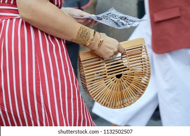 MILAN - JUNE 16: Woman with wooden bag, white and red striped dress and golden Cartier bracelets before Les Hommes fashion show, Milan Fashion Week street style on June 16, 2018 in Milan.
