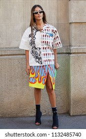 MILAN - JUNE 17: Gilda Ambrosio with white Prada shirt with lipstick decoration and skirt with flames before Prada fashion show, Milan Fashion Week street style on June 17, 2018 in Milan.