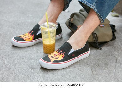 MILAN - JUNE 17: Man with black Vans shoes with flames design and orange juice before Emporio Armani fashion show, Milan Fashion Week street style on June 17, 2017 in Milan.