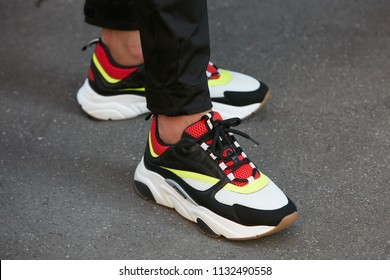 MILAN - JUNE 17: Man with white, black and red sneaker shoes before Isabel Benenato fashion show, Milan Fashion Week street style on June 17, 2018 in Milan.
