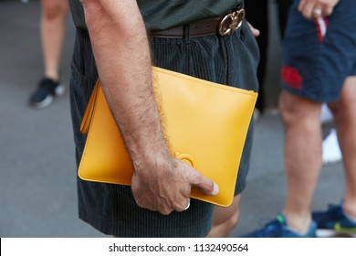 MILAN - JUNE 17: Man with yellow leather Salvatore Ferragamo bag and velvet trousers before Isabel Benenato fashion show, Milan Fashion Week street style on June 17, 2018 in Milan.