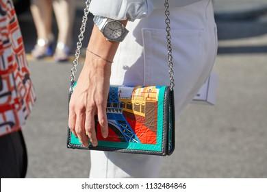 MILAN - JUNE 17: Woman with Audemars Piguet Royal Oak watch and colorful Balenciaga bag with Paris design before Prada fashion show, Milan Fashion Week street style on June 17, 2018 in Milan.