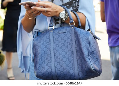 216a9739123 MILAN - JUNE 17  Woman with blue leather Gucci bag checking smartphone  before Diesel Black