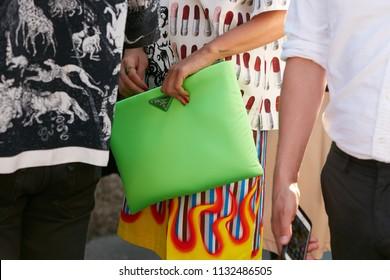 MILAN - JUNE 17: Woman with green Prada bag and skirt with flames before Prada fashion show, Milan Fashion Week street style on June 17, 2018 in Milan.