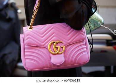 MILAN - JUNE 17: Woman with Gucci pink leather bag with golden chain before Versace fashion show, Milan Fashion Week street style on June 17, 2017 in Milan.