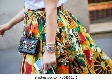 MILAN - JUNE 17: Woman with yellow, red and orange floral skirt, jewel bag and Rolex Datejust before Versace fashion show, Milan Fashion Week street style on June 17, 2017 in Milan.