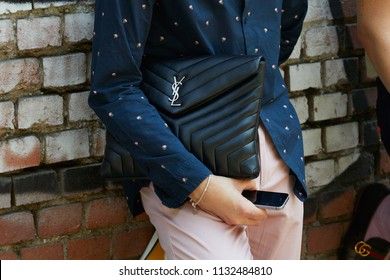 MILAN - JUNE 18: Man with Yves Saint Laurent black leather bag and pink trousers before Fendi fashion show, Milan Fashion Week street style on June 18, 2018 in Milan.