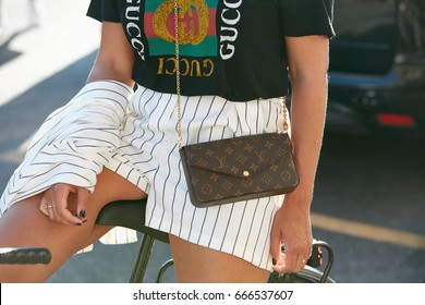MILAN - JUNE 18: Woman with black Gucci t-shirt and Louis Vuitton bag before Prada fashion show, Milan Fashion Week street style on June 18, 2017 in Milan.