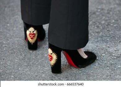 MILAN - JUNE 18: Woman with black velvet Louboutin high heel shoes with heart design before Prada fashion show, Milan Fashion Week street style on June 18, 2017 in Milan.