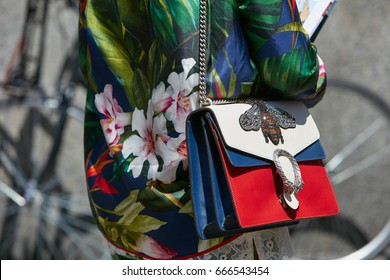 MILAN - JUNE 18: Woman with blue, red and white Gucci bag and silk floral shirt before Salvatore Ferragamo fashion show, Milan Fashion Week street style on June 18, 2017 in Milan.