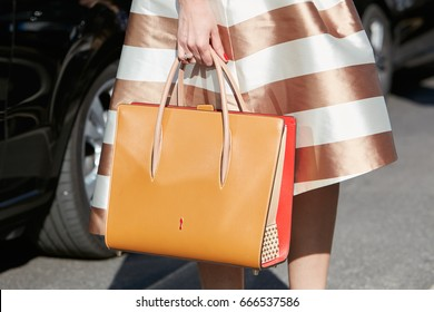 MILAN - JUNE 18: Woman with brown and red Louboutin bag and bronze and white striped dress before Prada fashion show, Milan Fashion Week street style on June 18, 2017 in Milan.