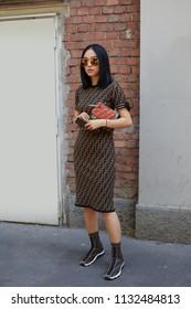 MILAN - JUNE 18: Woman with Fendi dress and bag before Fendi fashion show, Milan Fashion Week street style on June 18, 2018 in Milan.