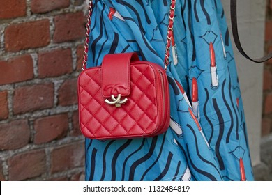 MILAN - JUNE 18: Woman with red Chanel leather bag and blue dress with lipstick and abstract face design before Fendi fashion show, Milan Fashion Week street style on June 18, 2018 in Milan.