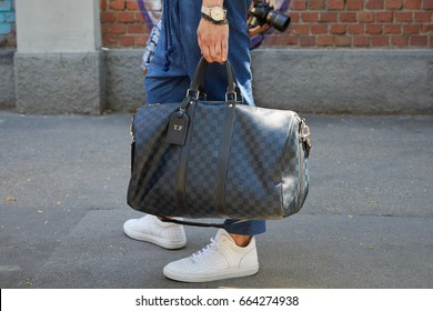 MILAN - JUNE 19: Man with gray checkered Louis Vuitton bag before Fendi fashion show, Milan Fashion Week street style on June 19, 2017 in Milan.