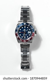 Milan, Lombardy, Italy - December 02, 2020: Rolex GMT-Master II watch, Baselworld 2018 edition with Pepsi red and blue ceramic bezel, on Rolex Oyster bracelet on white background with shadow