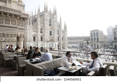 MILAN, LOMBARDY, ITALY-OCTOBER 23, 2019: outdoor terrace restaurant on top of Duomo square, with the Duomo cathedral in the background, in downtown Milan.