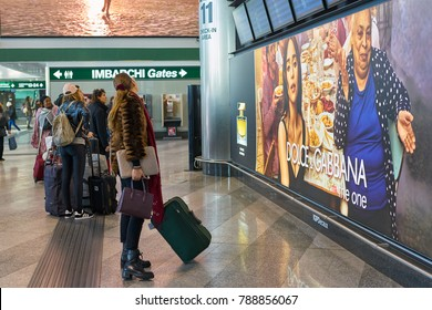MILAN MALPENSA, ITALY - CIRCA NOVEMBER, 2017: passengers standing in front of the flight information display monitors at Milan-Malpensa airport.