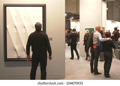 MILAN - MARCH 27: Man looks at paintings galleries during MiArt ArtNow, international exhibition of modern and contemporary art March 27, 2010 in Milan, Italy.