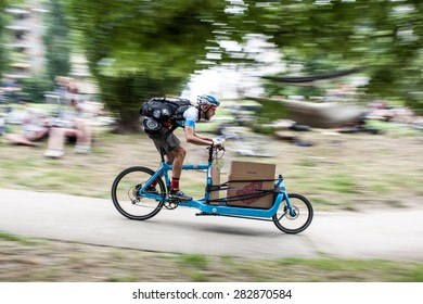Milan, may 31, 2015 - Urban messenger competes with a cargo bike in the European Cycle Messenger Championship, disputed on an urban circuit of Milan.