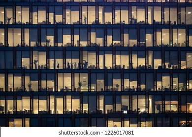 MILAN - NOV 8: Rows of windows with people working in the interior of an office building at night in Milan, Italy on November 8, 2018. Concept for employment, business, corporate, working, modern life