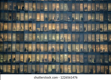 MILAN - NOV 8: view of windows with people working in the interior of an office building at night in Milan, Italy on November 8, 2018. Concept for employment, business, corporate, working, modern life