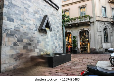 Milan Pertini Monument Fountain in via Montenapoleone with Shop. Long Exposure