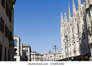 Milan piazza del Duomo -  perspective on side of gothic Cathedral and historc buildings exterior of the square. Blue sky background, top landmark Milan city.