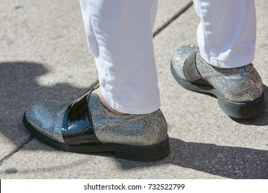 MILAN - SEPTEMBER 20: Man with silver glitter shoes and white trousers before Alberto Zambelli fashion show, Milan Fashion Week street style on September 20, 2017 in Milan.
