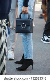 MILAN - SEPTEMBER 20: Woman with blue jeans trousers, black high heel boots and bag before Alberta Ferretti fashion show, Milan Fashion Week street style on September 20, 2017 in Milan.