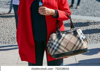 MILAN - SEPTEMBER 20: Woman with Burberry bag and red coat before Alberto Zambelli fashion show, Milan Fashion Week street style on September 20, 2017 in Milan.