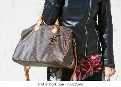 MILAN - SEPTEMBER 20: Woman with Louis Vuitton brown bag and black leather jacket before Alberto Zambelli fashion show, Milan Fashion Week street style on September 20, 2017 in Milan.
