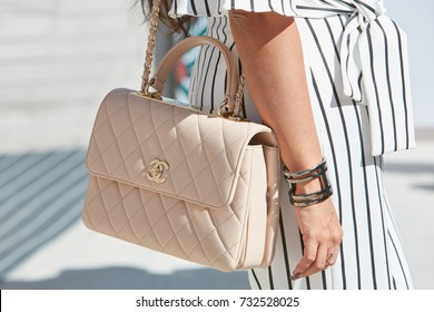 MILAN - SEPTEMBER 20: Woman with pale pink Chanel bag and black and white striped trousers before Alberto Zambelli fashion show, Milan Fashion Week street style on September 20, 2017 in Milan.
