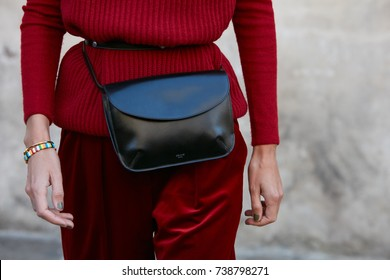 MILAN - SEPTEMBER 21: Woman with black leather Celine bag and red velvet trousers before Max Mara fashion show, Milan Fashion Week street style on September 21, 2017 in Milan.