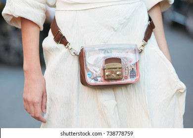MILAN - SEPTEMBER 21: Woman with Furla transparent bag and white dress before Prada fashion show, Milan Fashion Week street style on September 21, 2017 in Milan.