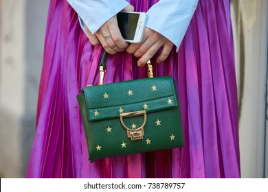 MILAN - SEPTEMBER 21: Woman with green Coccinelle leather bag with golden stars and fuchsia metallic skirt before Fendi fashion show, Milan Fashion Week street style on September 21, 2017 in Milan.