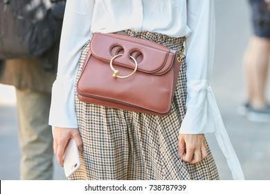 MILAN - SEPTEMBER 21: Woman with Jw Anderson brown leather bag and white shirt before Fendi fashion show, Milan Fashion Week street style on September 21, 2017 in Milan.