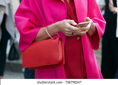 MILAN - SEPTEMBER 21: Woman looking at smartphone with red leather bag and fuchsia pink coat before Luisa Beccaria fashion show, Milan Fashion Week street style on September 21, 2017 in Milan.